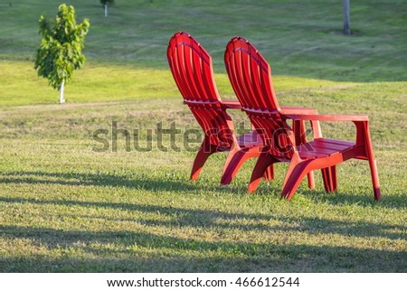 Two Red Adirondack Chairs on the Lawn