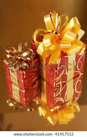 Two red and gold gifts on gold background with reflection.