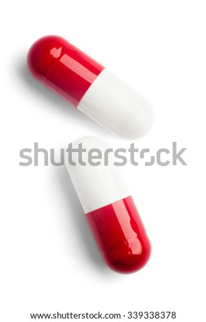Two red and white capsules on white background - stock photo