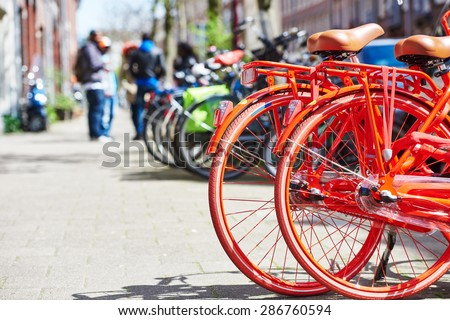 Two red bicycle on the city street near hotel in Amsterdam - stock photo