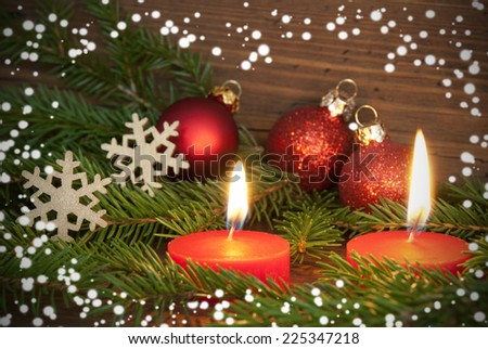 Two Red Burning Candles with Christmas or Winter Decoration as Winter, Christmas or Advent Background with Copy Space - stock photo
