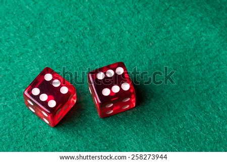 two red casino dices on green table