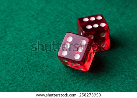 two red casino dices on green table - stock photo