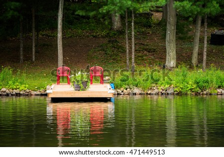 Two red chairs on a dock against a dark forest