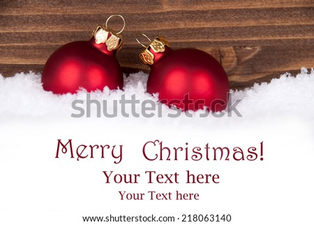 Two Red Christmas Balls in the Snow in front of Wooden Background with Christmas Greetings and Copy Space for your Text - stock photo