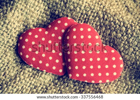 Two red decorative hearts on sackcloth background.Vintage style. - stock photo