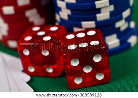 two red dice and poker chips on green table, close up - stock photo