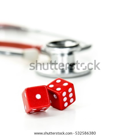 Two red dice and stethoscope close-up against a light background with copy space. Concept image for postcode lottery healthcare, receiving better health care depending where you live.