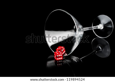 two red dice in a cocktail glass on black background with space for text - stock photo