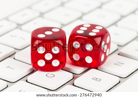 Two red dice on keyboard, online casino concept - stock photo