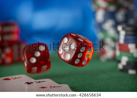 Two red dice rotates in the air, casino chips, cards on green felt - stock photo