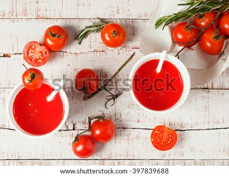 two red drinks with fresh tomato and rosemary on white wood. Healthy lifestyle, vegan background. Detox - stock photo