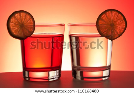 Two red drinks with lime slices on white table with red gradient backdrop. - stock photo