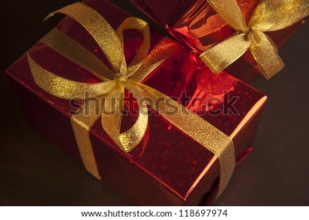 two Red foil gift with gold translucent bow on black background. - stock photo