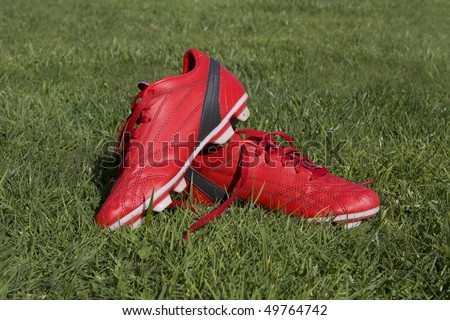 Two red football shoes on the grass - stock photo