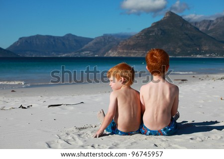 Two red haired boys or brothers sitting alone together on deserted beach happy and content looking at beautiful scenery