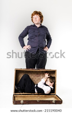 Two red-haired brothers playing with vintage suitcase - stock photo