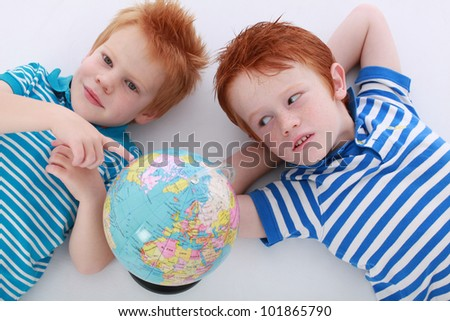 Two red head boy brothers lying together  and looking and smiling at geographic world atlas globe isolated on white