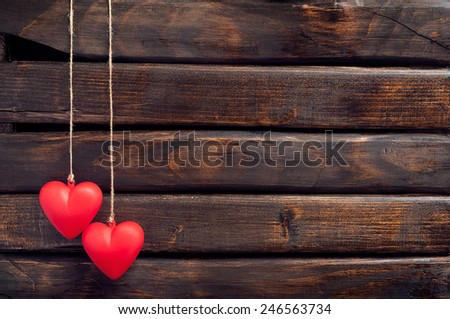 Two red heart pendant on a background of wood. Heart pendant. Red heart.  Space for text. Valentine's Day. Valentine day. Eighth of March. International Women's Day. - stock photo