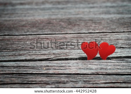 Two red heart shape, symbol of love, stand together on grunge wood background. Abstract background in romantic love concept for Valentine's day season. Vintage style. - stock photo