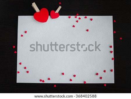Two red hearts and many small hearts with a piece of paper on the dark wooden background. Empty space for text or photo. Picture frame. Valentines Day background. Valentine's Day theme. - stock photo