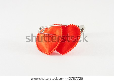 Two red hearts, bound among themselves a pin