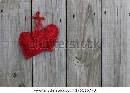 Two red hearts hanging with wood background - stock photo