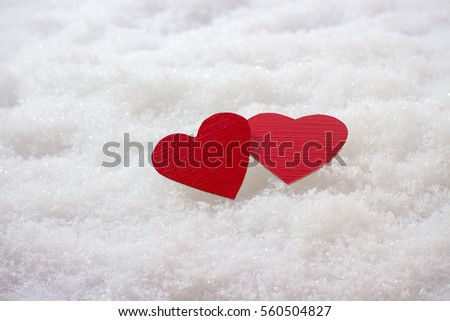 Two red hearts in the snow, top view
