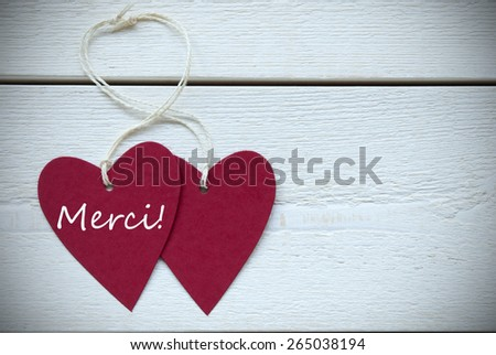 Two Red Hearts Label With White Ribbon On White Wooden Background With French Text Merci Means Thank You Vintage Retro Or Rustic Style With Frame - stock photo