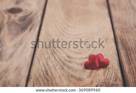Two red hearts on a old wooden background - vintage toning - stock photo