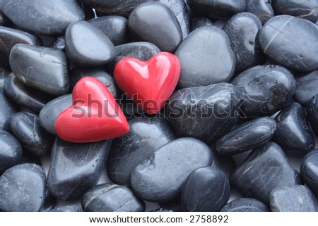 Two red hearts on a pebble background - stock photo