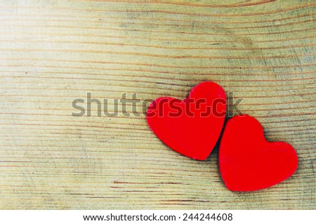 Two red hearts on an impressive wooden background. - stock photo
