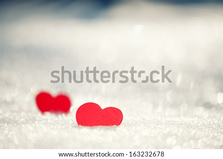 Two red hearts on glittering snow. - stock photo