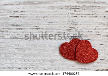 two red hearts on white wooden background
