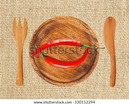 Two red hot chilly peppers on wooden plate over burlap - stock photo