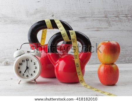 Two red kettlebells with measuring tape, apples, and vintage clock on rustic white wooden table. Healthy diet and fitness concept. - stock photo