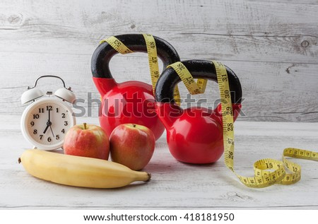 Two red kettlebells with measuring tape, apples, banana, and vintage clock on rustic white wooden table. Healthy diet and fitness concept. - stock photo