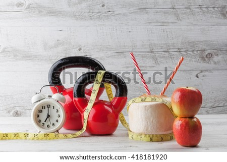Two red kettlebells with measuring tape, drinking coconut, straws, apples, and vintage clock on rustic white wooden table. Healthy diet and fitness concept. - stock photo