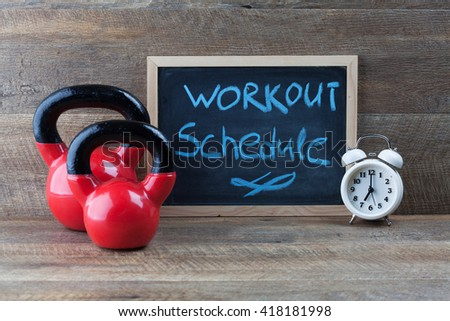 Two red kettlebells with vintage clock and small blackboard on wooden table. Workout schedule concept. - stock photo