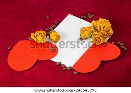 Two red paper hearts in the envelope with several dried yellow roses and coffee beans - stock photo