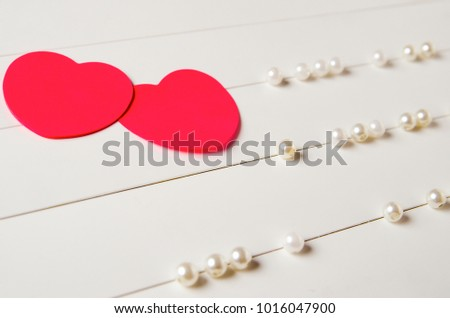 two red paper hearts on a light striped background with pearl beads