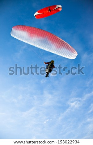 Two red paragliders flying in blue sky. From below. - stock photo