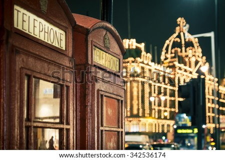 two red phone boxes at night in Knightsbridge against lit shopping centre - stock photo