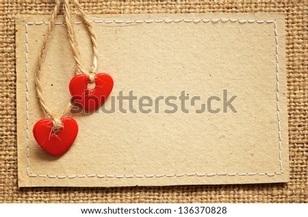 Two red plastic hearts and carton card on a canvas background - stock photo