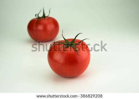 Two red ripe tomato with long sepal leaves still intact. Isolated on natural white background. - stock photo