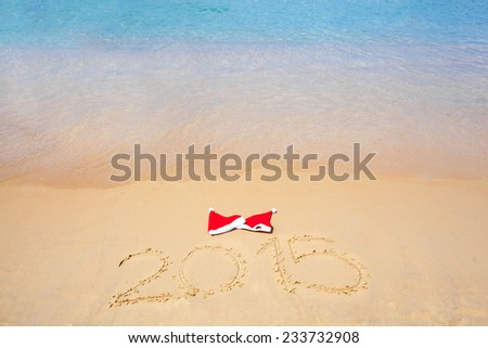 two red santa hats on beach and 2015 text - stock photo