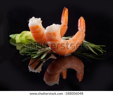 Two red shrimps tails with green fresh rosemary and lettuce on the black - stock photo