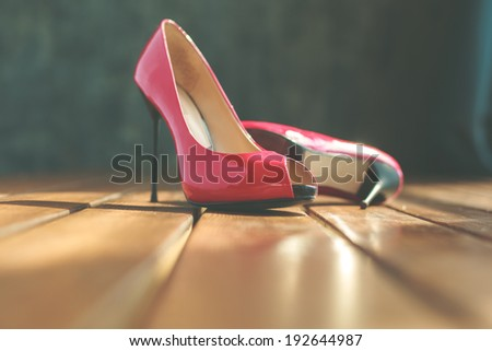 Two red stilettos over wooden planks floor