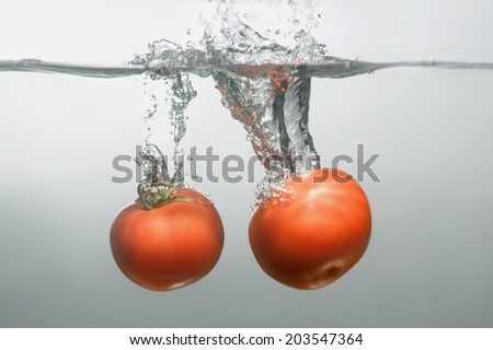 Two red tempting tomatoes dropped into the water spreading little bubbles
