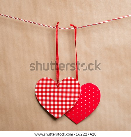 Two red textured hearts hanging on a ribbon. Old brown paper background - stock photo